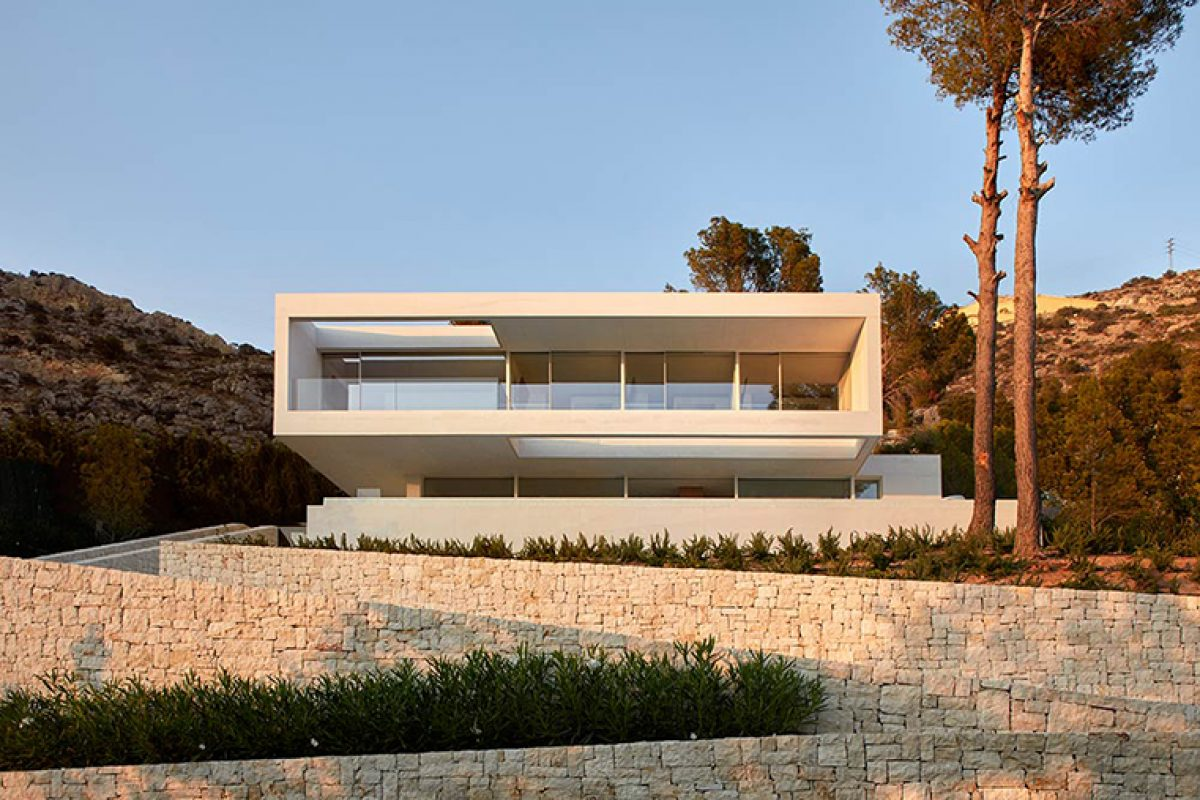 Oslo House by Ramón Esteve, a concrete block surrounded by Mediterranean pine trees and vegetation